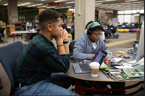 Two students study together at laptops in a library, surrounded by coffee cups and snacks.