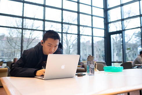 A student studies at a laptop in an atrium with floor-to-ceiling windows in the background.