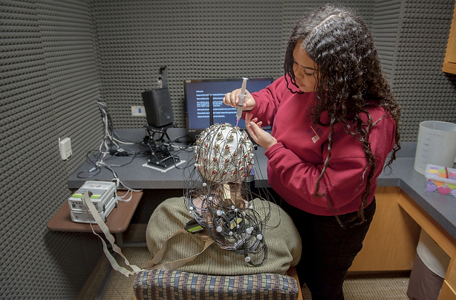 A student performs a neuroscience experiment on another student in a lab
