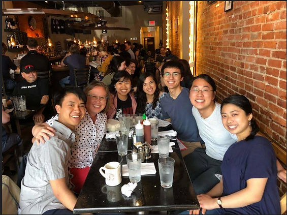 Six students and a faculty member sit together at a restaurant table for dinner