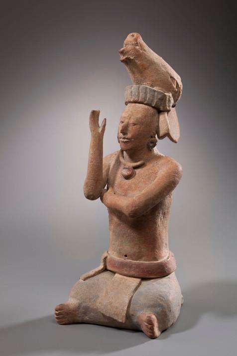 Statuette représentant un personnage assis ceint d'une haute coiffure zoomorphe (cerf ?)
