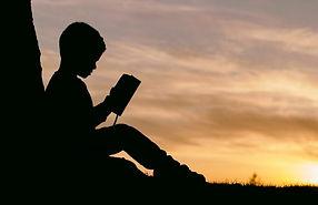 silohette of kid reading book - Rachel K