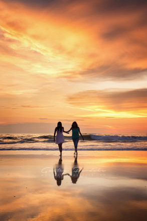 Beautiful landscape photograph with two silhouttes at sunset on a sea beach in India