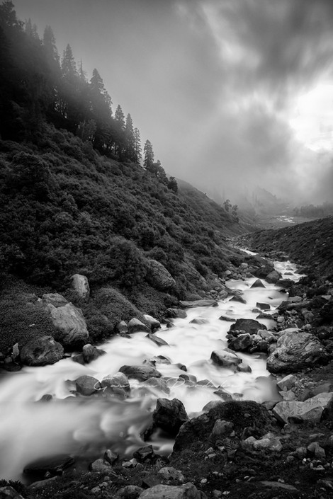 Artistic black and white image of a stream with fog in the high Himlayan mountains of India