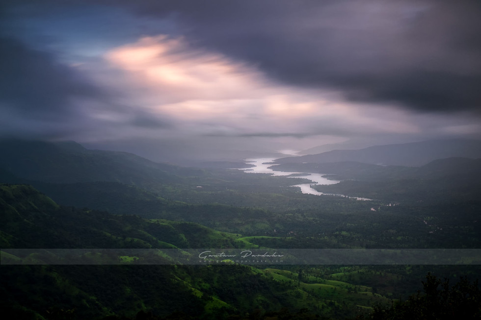 Artistic landscape photograph showing clouds over post monsoon green Western Ghats in India