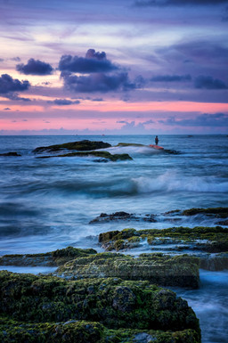 Beautiful landscape photograph with a sole figure standing strong on a rock in the sea at sunset in Goa, India