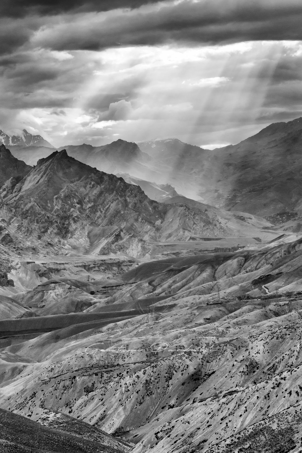 Artistic black and white landscape photo of a break in the clouds in the high Himlayan mountains of Ladakh India