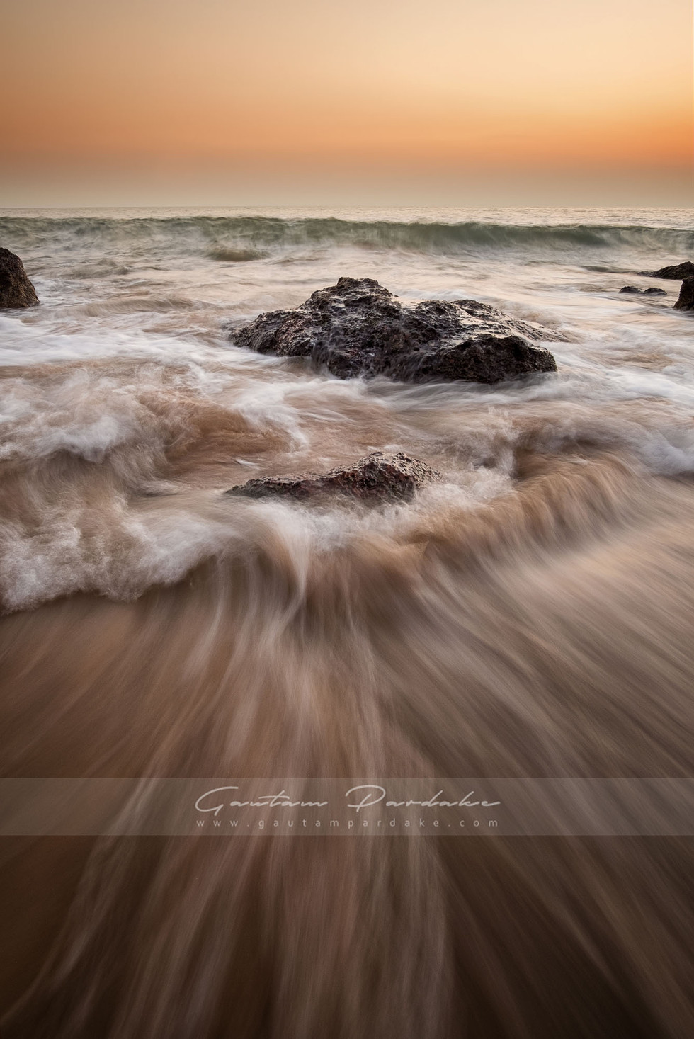 Powerful landscape photograph with crashing waves on an Indian beach at sunset