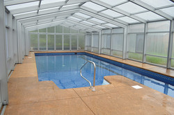 Inground swimming pool with lap lane and retractable glass enclosure