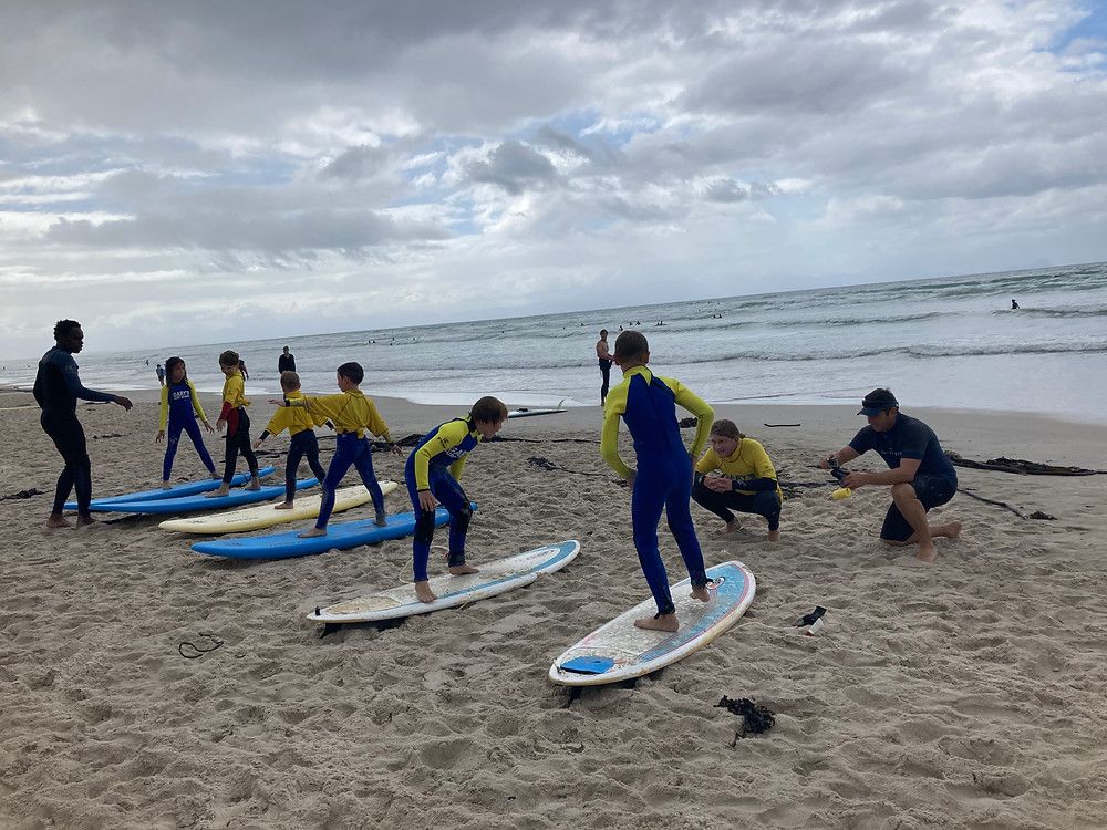 Surf party with Gary's surf school in Cape Town, South Africa. Teaching children to surf for an adventurous birthday party