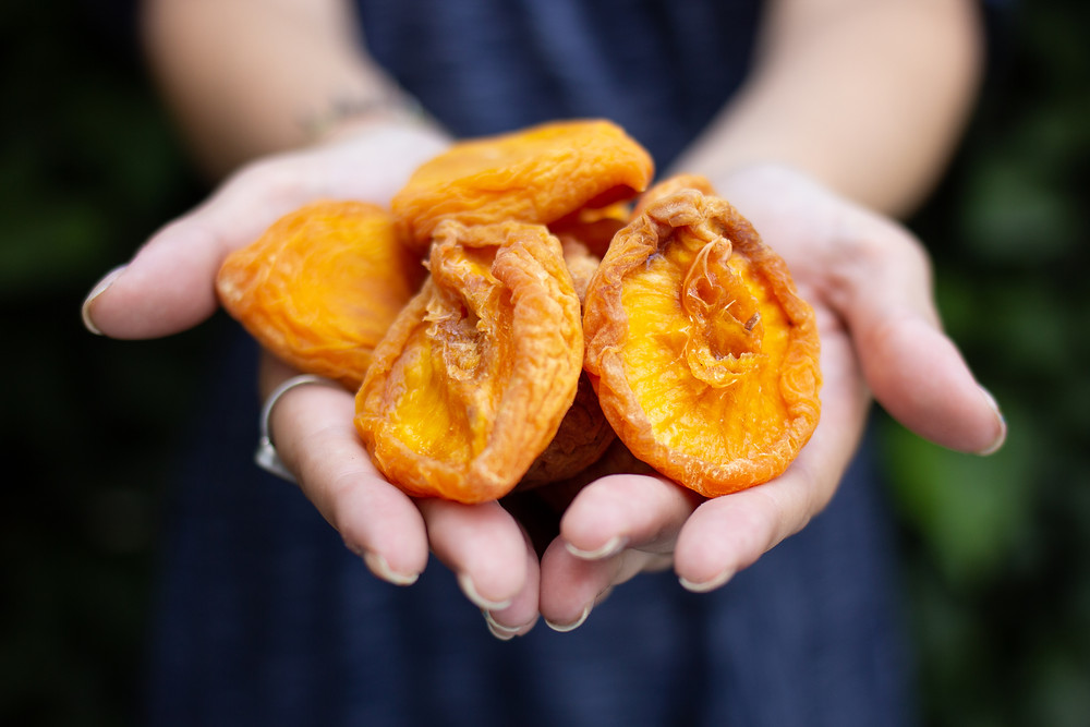 dried apricot . healthy snack options. in hands