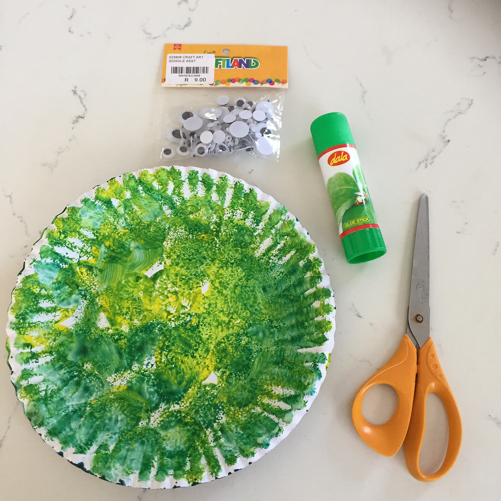 Once paint is dry on plate. Flat lay of products needed for next steps to make fish. Googly eyes, glue, scissors.