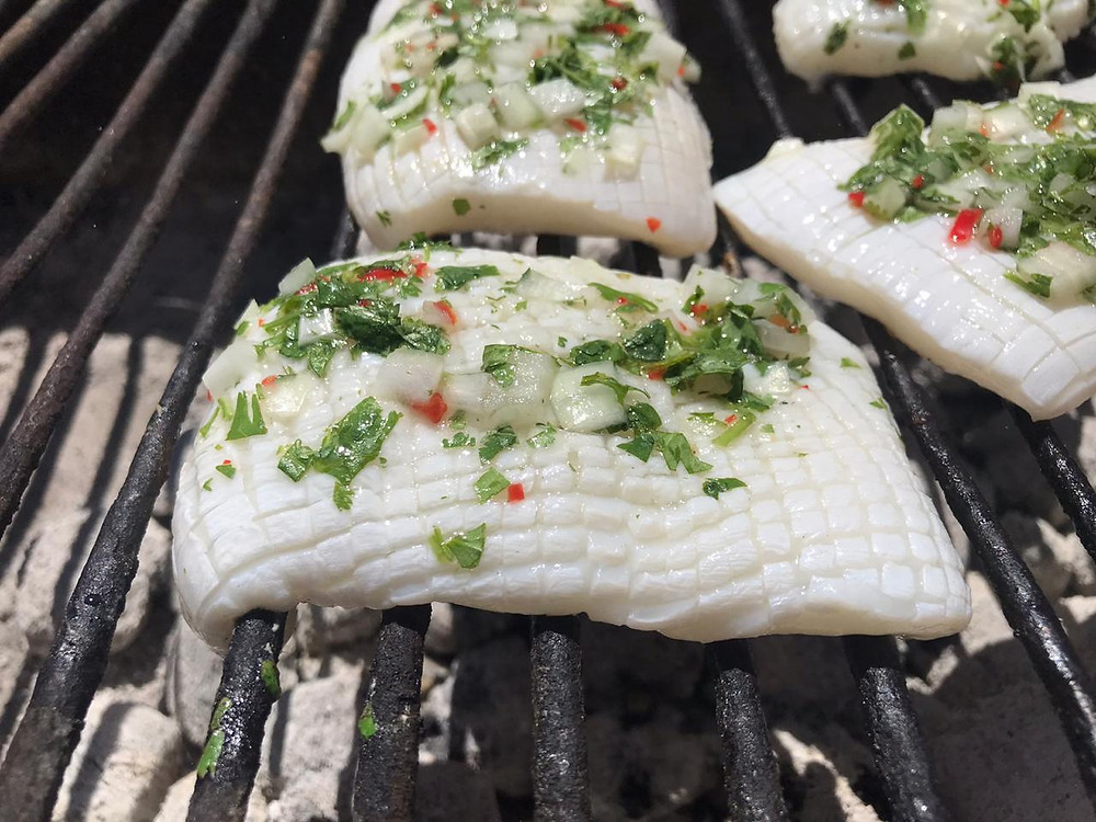 Calamari Steaks on grill over coals.