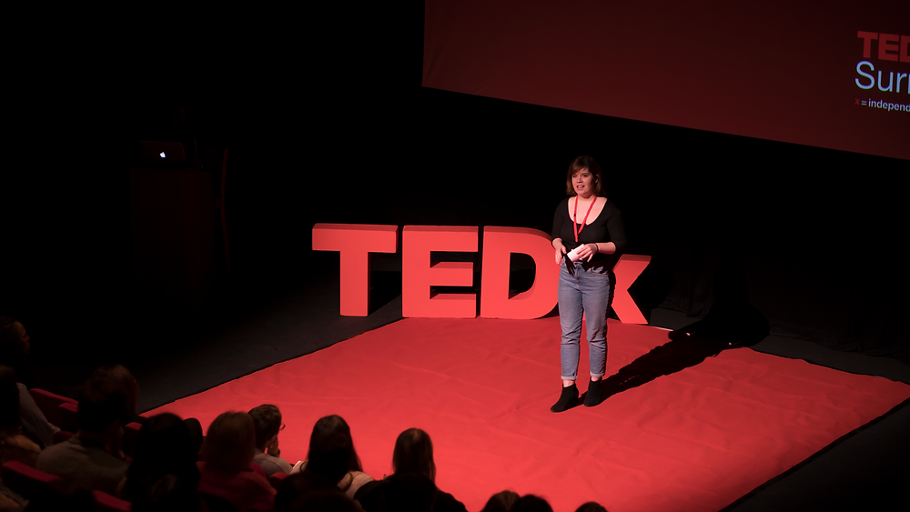 Co-founder Bethany Dawson is delivering a TEDx Talk on a red carpet with a red TEDx sign behind her. She is wearing blue jeans and a black top and talking passionately.