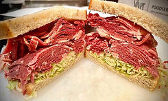 Deli sandwich,Check The Ice, corned beef, mustard, lettuce, tomato, red onion piled high on rye bread.