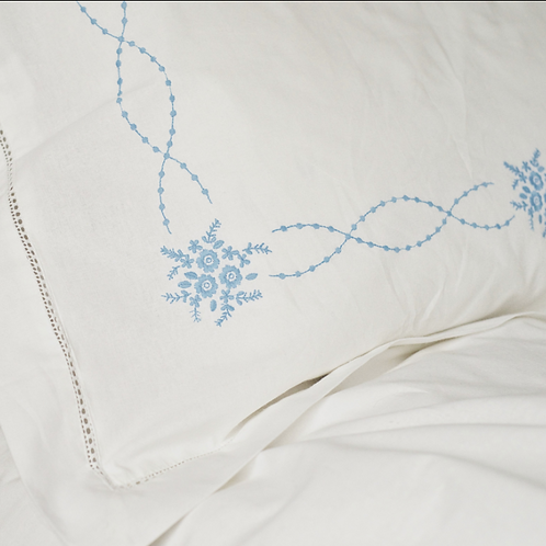 A pair of blue embroidered pillow cases