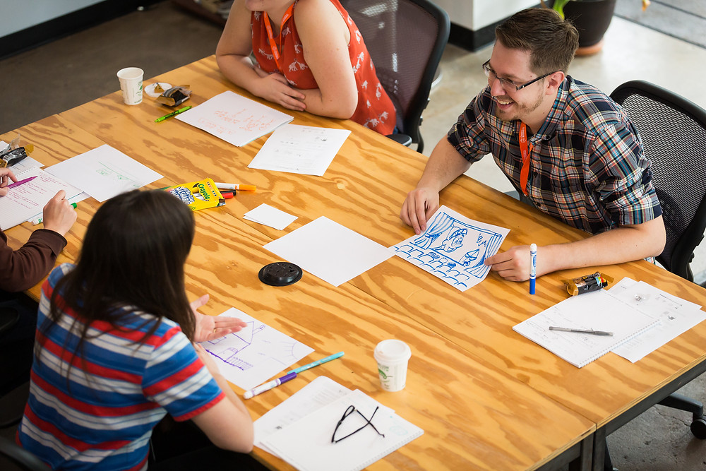 creative professionals at table developing skills in artistry business marketing and storytelling