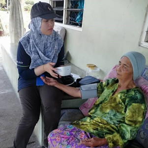 Azziana taking blood pressure during the survey data collection