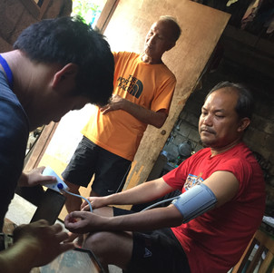 Dom taking blood pressure to a participant during the survey data collection