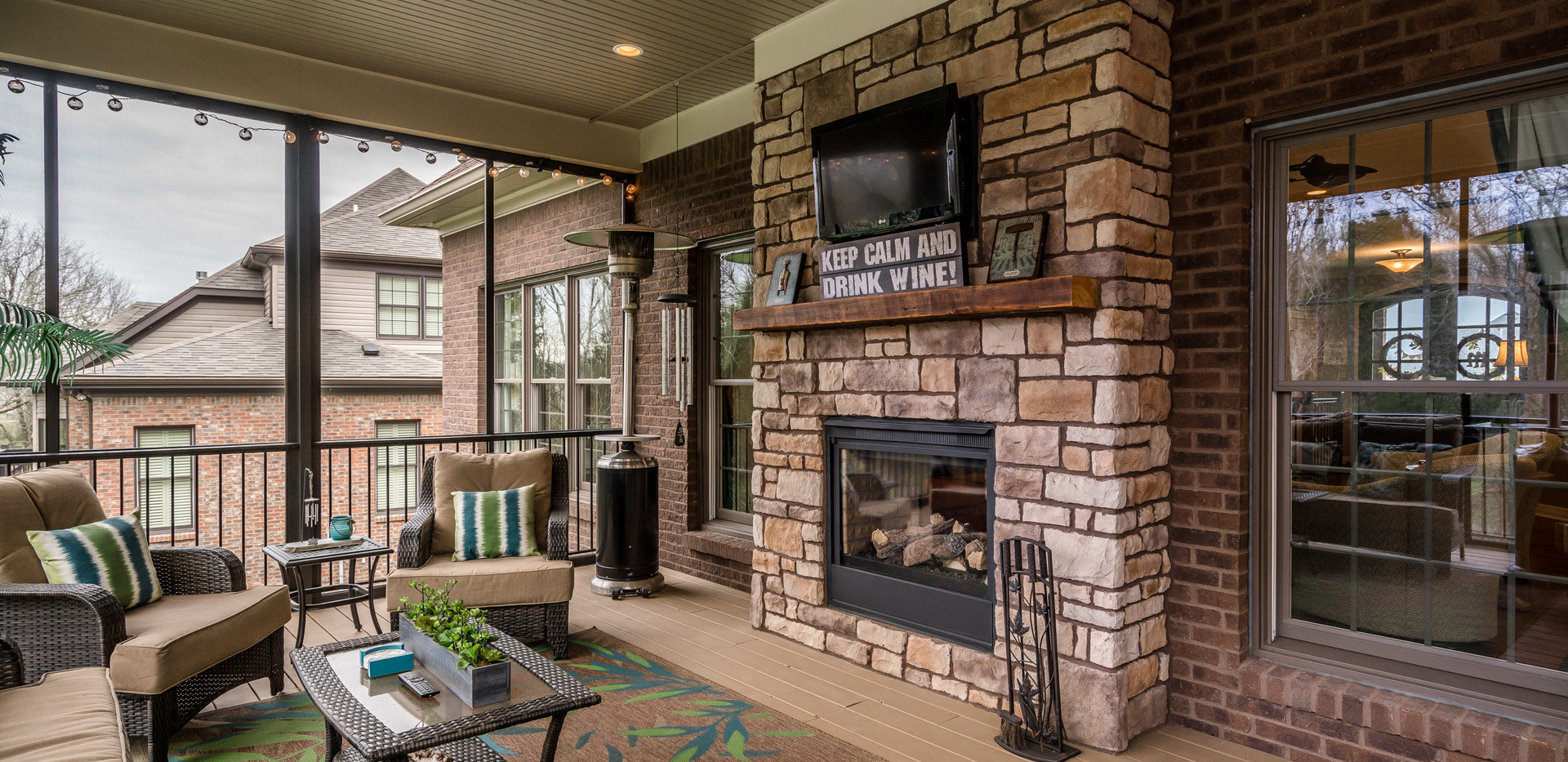 A covered screened in deck with fireplace is perfect for entertaining.