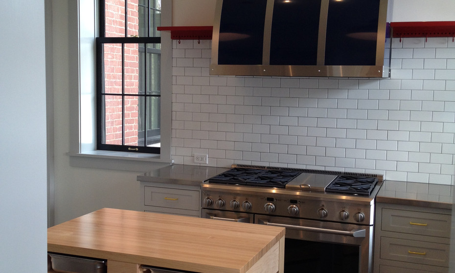 Modern Kitchen in a historic home.  Notice the laminate flooring that follows the floorplan, but turned on a 35-degree.  The custom hood fan, pot rack and small island complete this transformation.
