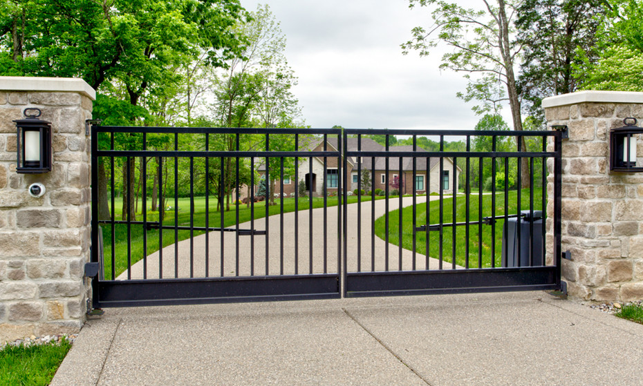 Privacy was a hot button for this homeowner after a long day at the office.  Custom gate with stone columns and lighting.