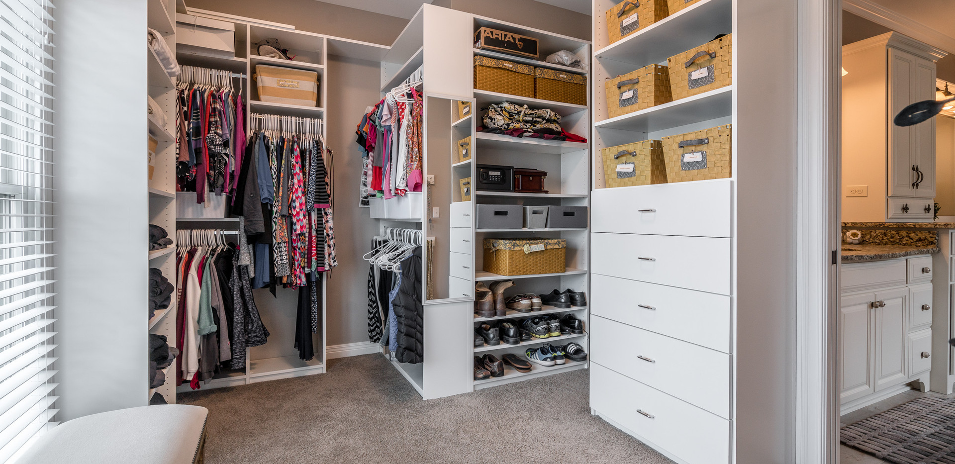Custom closet design by Closets By Design makes this closet feel like your own store to select your clothing ensemble each day.