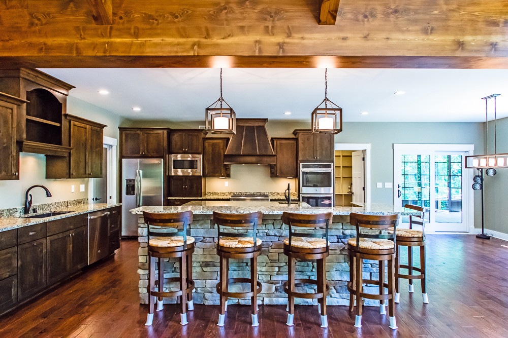 This open Kitchen layout overlooks the Great Room and has two islands.  The wood beams and manufactured stone place this home nicely within the acerage.