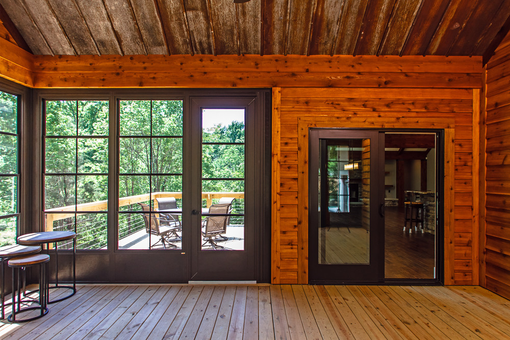 Reclaimed barn roofing has been installed on this outdoor deck area with Sunspace Weather Master vertical stacking windows.
