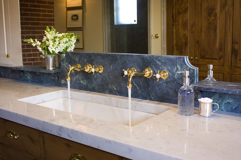 A custom vanity with custom granite splash, twin faucets and trough sink.