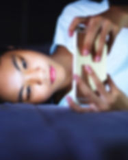 teen girl lying in bed at night and usin