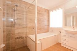 Main bathroom with stone tile finish