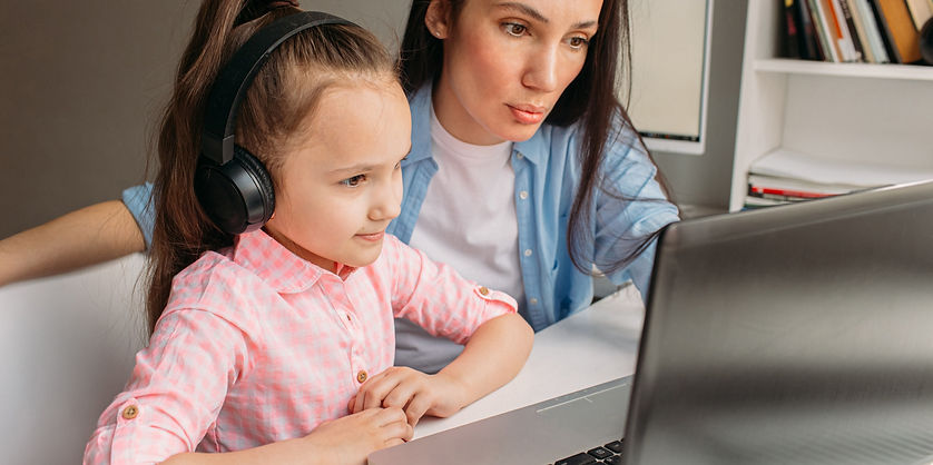 mom and girl with headphones joining online speech therapy