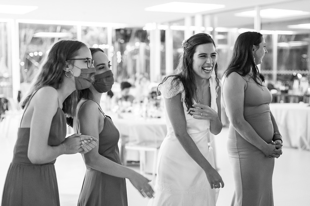 Bride laughs with bridesmaids