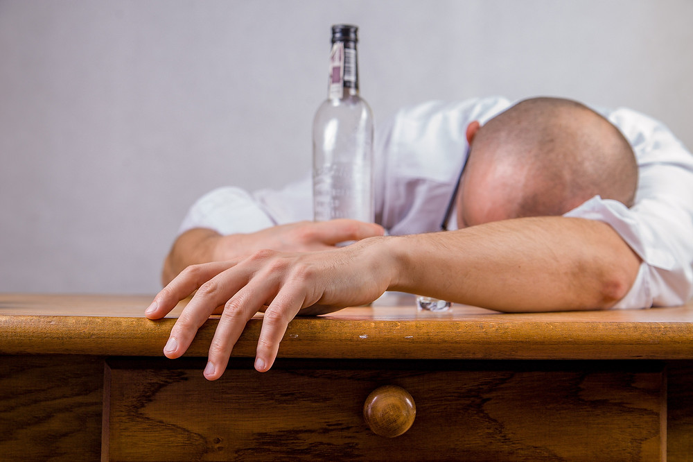 Man passed out on table with empty bottle