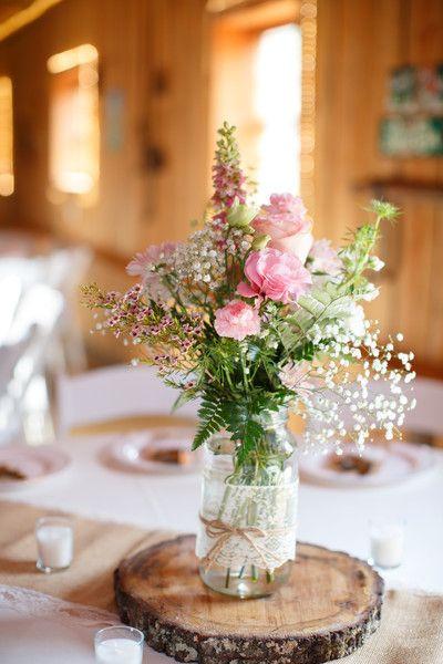 15 DIY mariage avec des bouteilles et pots en verre récupérés, pour un beau mariage écologique à petit budget. Centre de table pastel et champêtre avec rondin de bois, pot en verre et dentelle. Crédit photo : Jamie Blow photography