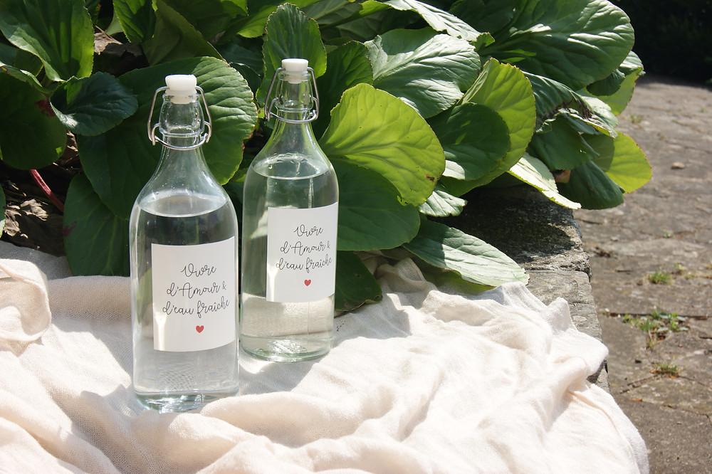 """Bouteille d'eau en verre avec étiquette """"vivre d'amour et d'eau fraîche"""". Comment rendre son mariage plus éco-responsable ? 10 objets à éviter et leurs alternatives"""