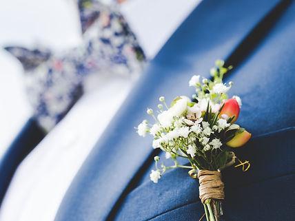 marié avec un noeud papillon aux motifs liberty et une boutonnière de fleurs