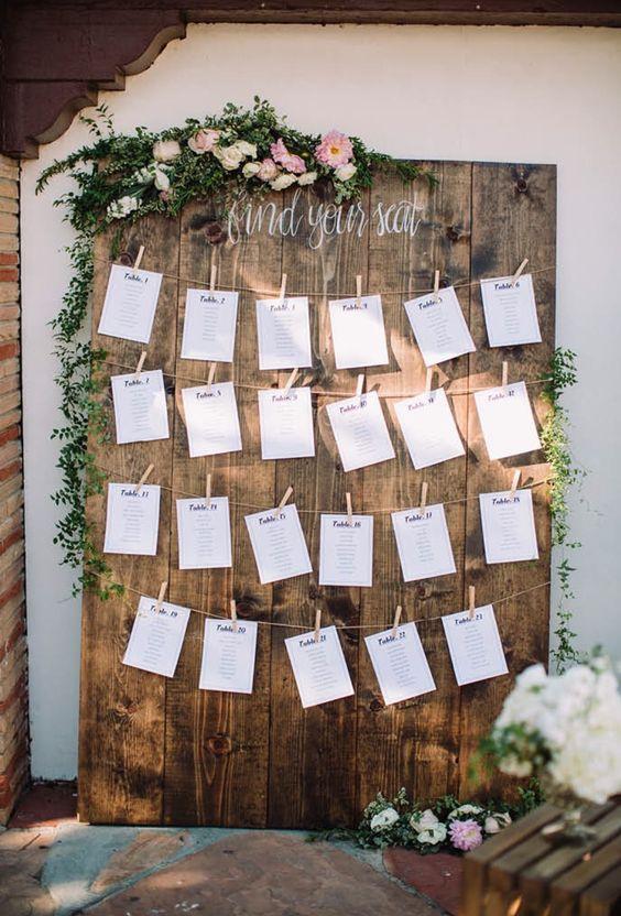 10 façons d'utiliser la pince à linge en bois dans votre décoration de mariage. Plan de table sur un support en bois avec des cartes suspendues par des pinces à linge et bois. #mariage #plandetable #champetre