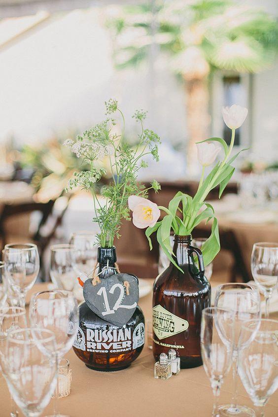 15 DIY mariage avec des bouteilles et pots en verre récupérés, pour un beau mariage écologique à petit budget. Centre de table réalisé à partir de bouteilles de bière artisanales pour un mariage folk, décontracté et décalé. Crédit photo : Brett & Tori photographers