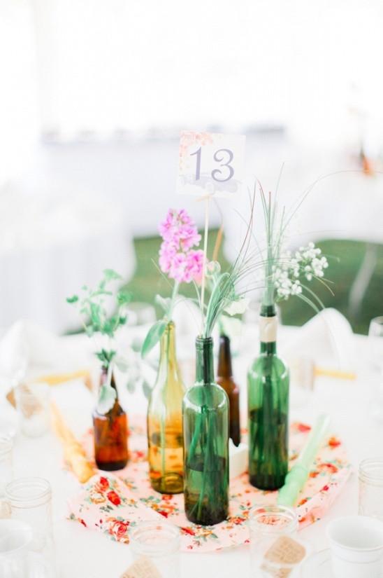 15 DIY mariage avec des bouteilles et pots en verre récupérés, pour un beau mariage écologique à petit budget. DIY centre de table avec des bouteilles de vin et de bière colorés. Crédit photo : Jordan Brittley
