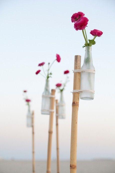 15 DIY mariage avec des bouteilles et pots en verre récupérés, pour un beau mariage écologique à petit budget. DIY allée de cérémonie de mariage par le blog Something Turquoise à partir de tiges de bambou et de bouteilles en verre. Crédit photo : Something Turquoise