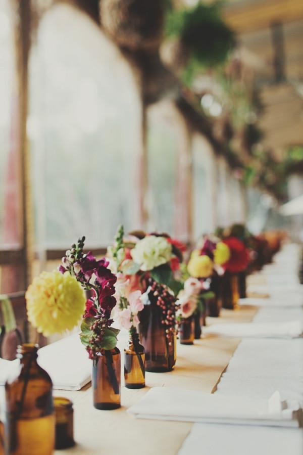 15 DIY mariage avec des bouteilles et pots en verre récupérés, pour un beau mariage écologique à petit budget. Chemin de table bohème réalisé à partir de bouteilles en verre ambrées et de fleurs colorées. Crédit photo : Jonathan Ong