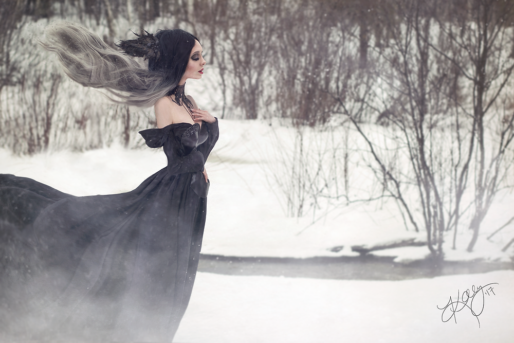 Gothic beauty with hair blowing in the wind, surrounded by winter landscape
