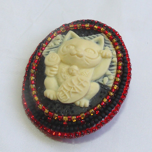 Cream Maneki-neko cameo brooch on black