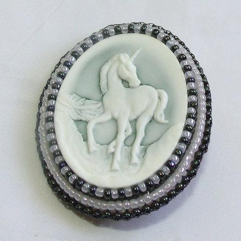 Prancing Unicorn cameo brooch on pale blue