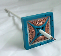 A handpainted drop spindle in white, gold, and turquoise lying on a table.