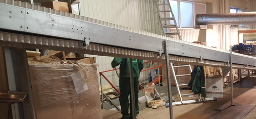 Product transfer conveyor from the production line and flow distribution into two packing lines