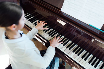 good student plays the piano at a music