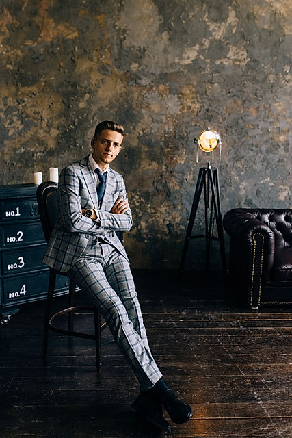 A man in a blue suit is sitting on a cha